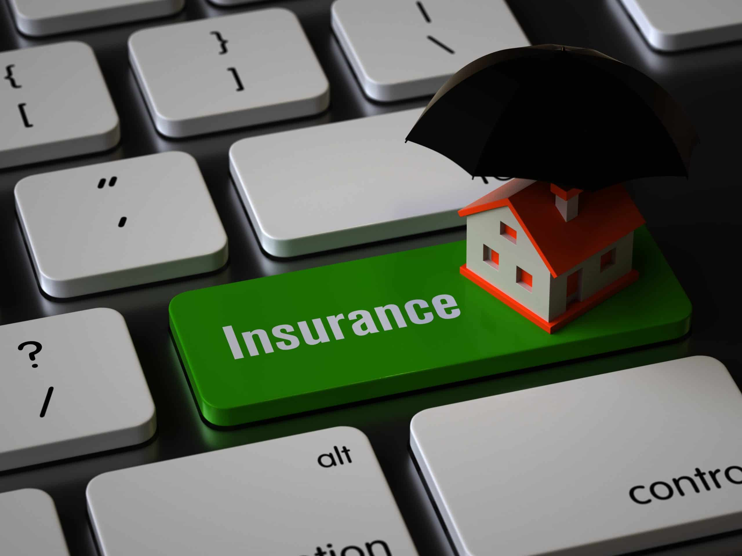 toy house under umbrella sitting on keyboard with large Insurance key