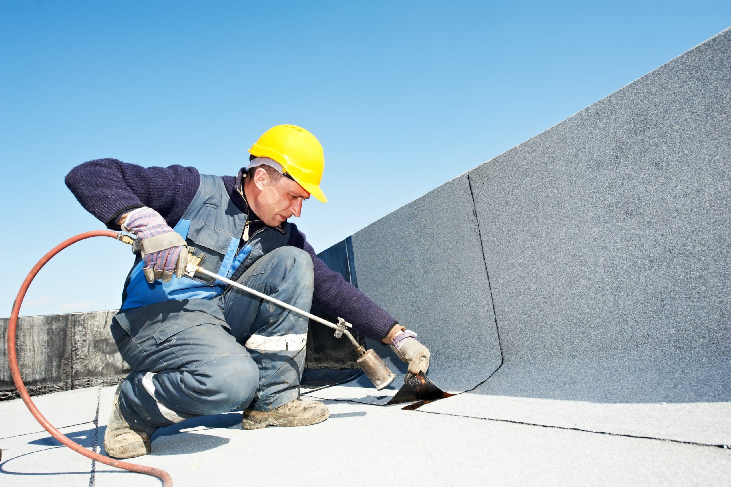 Roofer Working on a Flat Roof - Roofing Companies - Get Your Quote