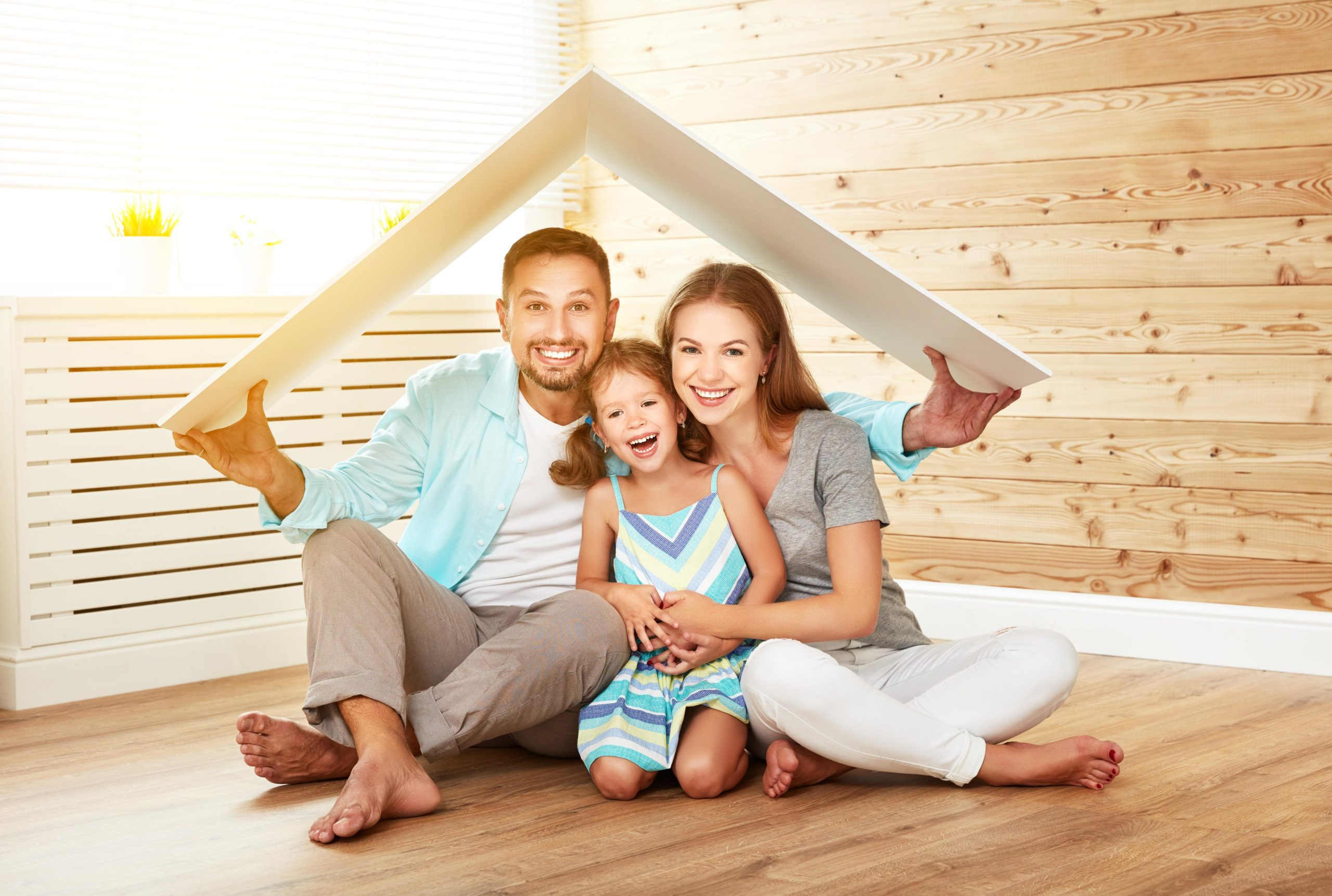 man holding small roof over himself, wife and daughter