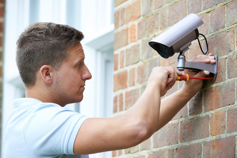 Man Installing a Security Camera - Find Home Security Companies Near You - Get Your Quote