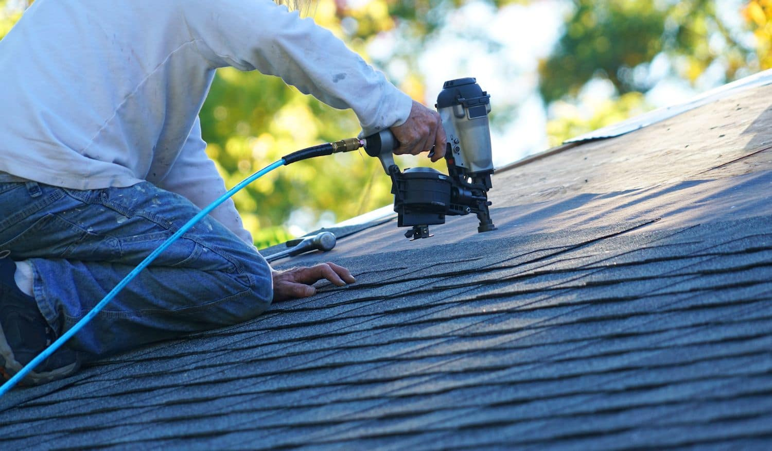 man using nail gun to put shingles on roof