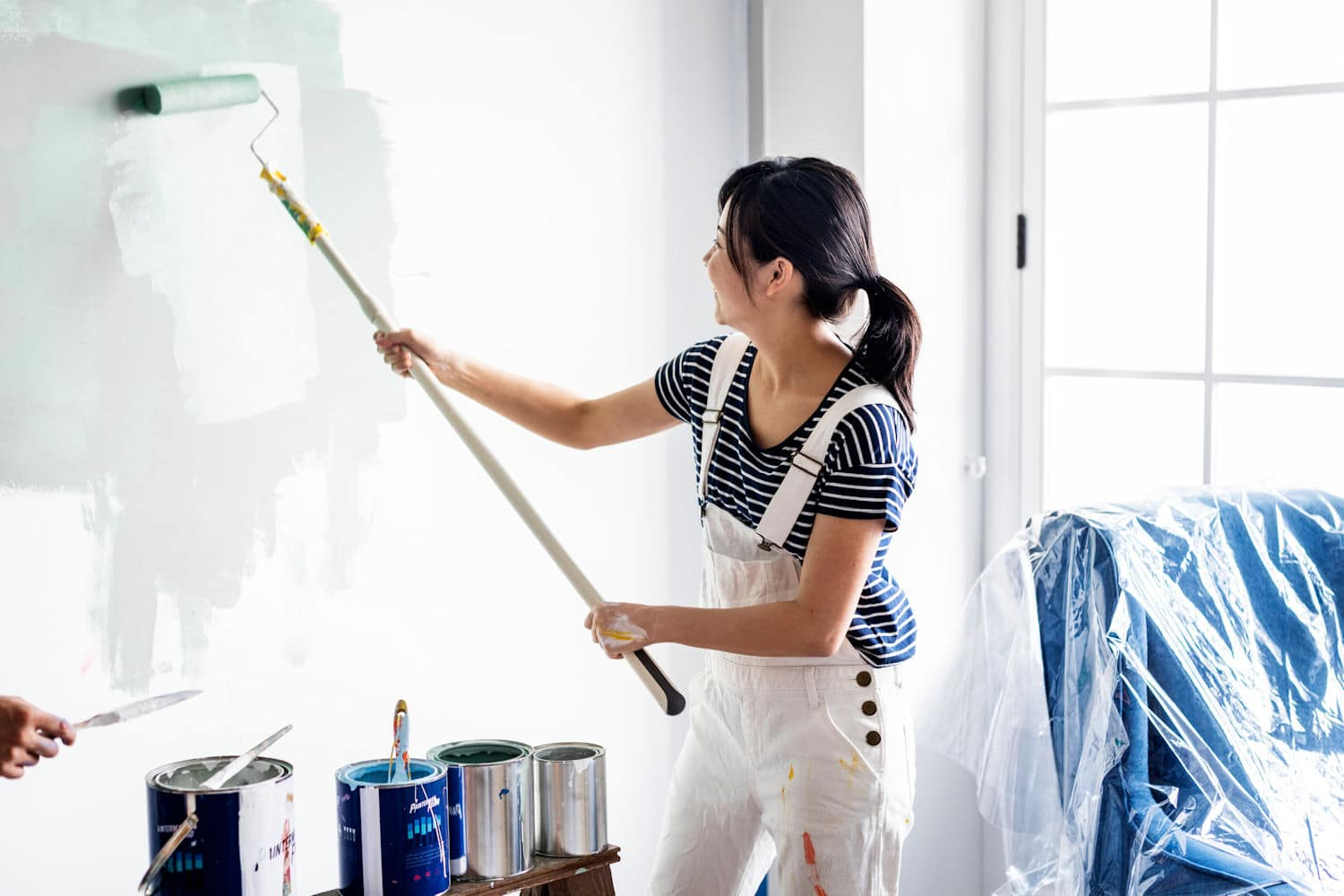 woman painting with roller