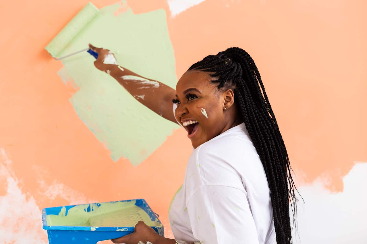 woman painting with a laugh and smile